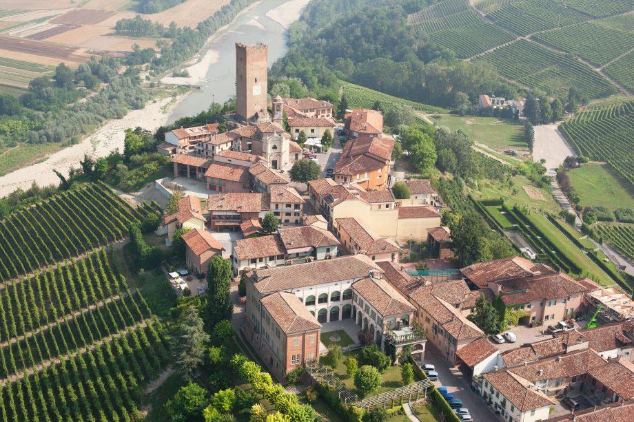 Dronefoto af Barbaresco by hvor man ser Torre di Barbaresco med floden Tanaro i baggrunden